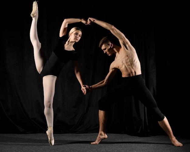 Pareja de ballet posando en zapatillas de punta y medias