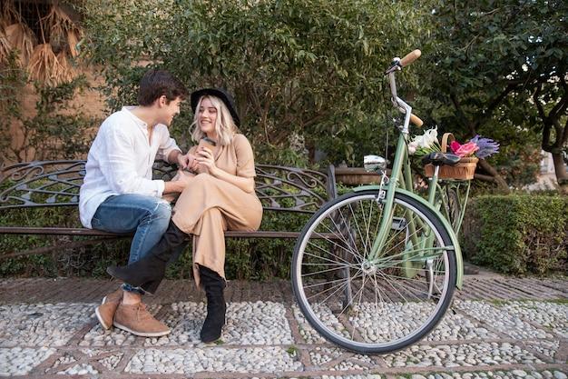 Pareja en el banco con bicicleta y flores.