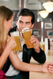 Pareja en el bar bebiendo cerveza coqueteando
