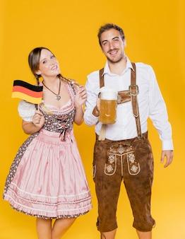 Pareja bávara tradicional con bandera y cerveza