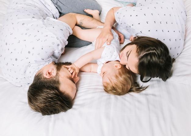 Pareja con bebé en la cama