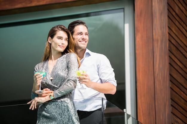 Pareja con bebidas de pie en el balcón en el resort