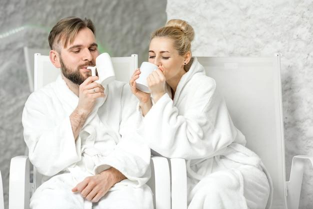 Pareja bebiendo agua mineral sentado en la sala de sal. aplicar terapia de sal en el spa