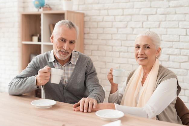 Pareja bebiendo café, tomados de la mano juntos en casa.