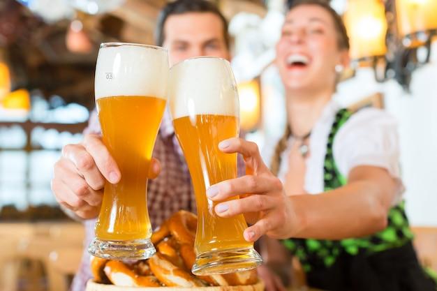 Pareja bebiendo cerveza de trigo en un restaurante bávaro