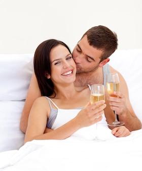 Pareja bebiendo champán en la cama en el día de san valentín
