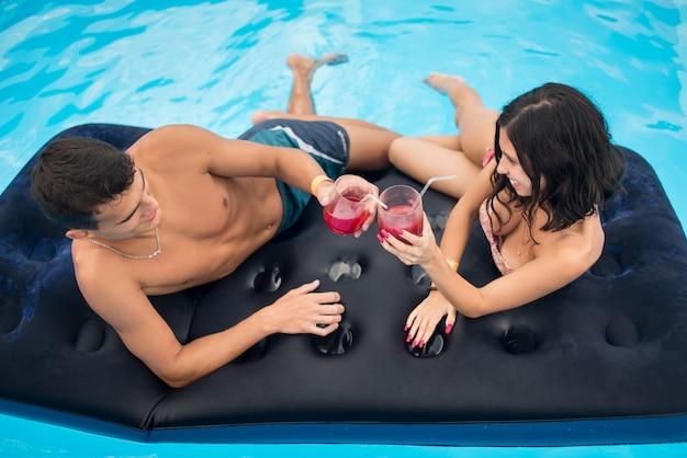 Pareja bebiendo cócteles en un colchón en la piscina