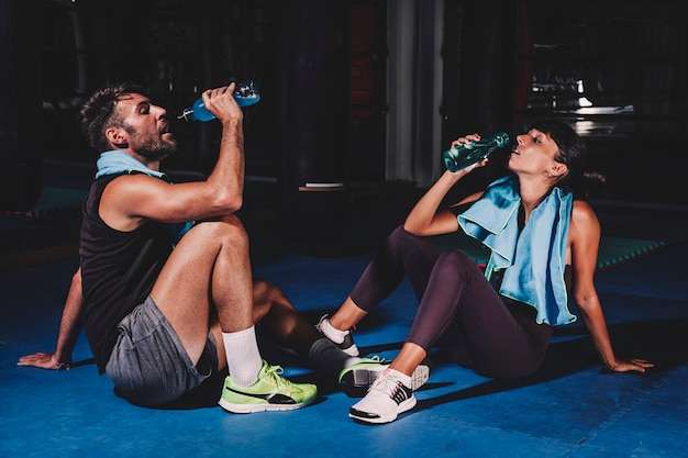 Pareja bebiendo en gimnasio