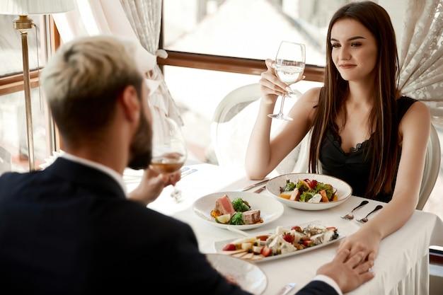 Pareja está bebiendo vino blanco en la cena romántica en el restaurante y tomados de la mano