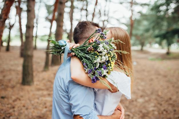 Pareja besa y se cubre con un ramo