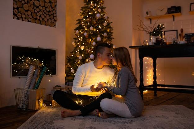 Pareja besándose en casa de navidad con guirnalda de luz mágica en manos