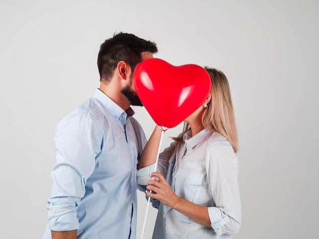 Pareja besándose detrás del globo para san valentín