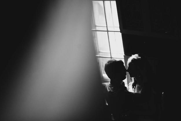 Pareja besandose en una habitación oscura