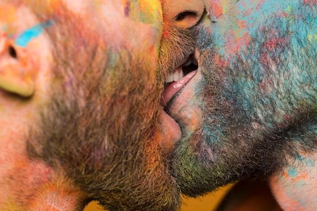 Pareja besándose de hombres homosexuales en pintura de arcoiris de colores.
