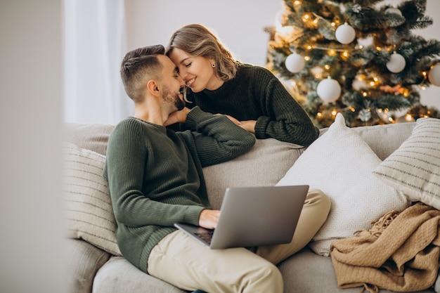 Pareja besándose junto al árbol de navidad, utilizando equipo portátil