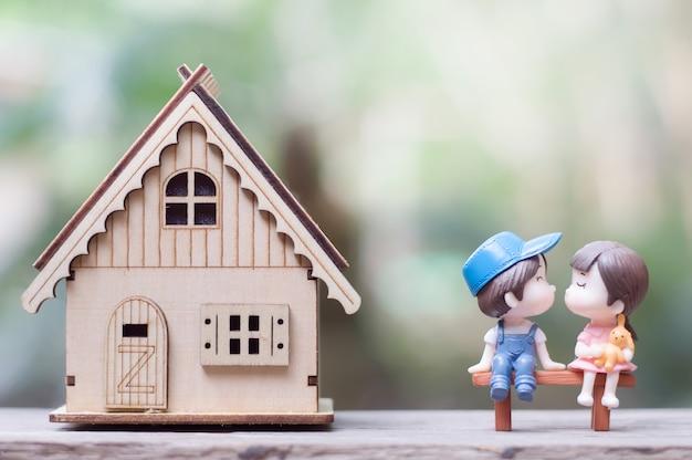 Pareja besándose sentada en el banco de madera junto a su casa