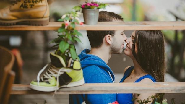 Pareja besándose a través de una estantería