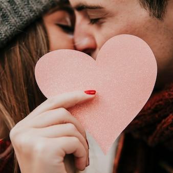 Pareja besándose y sosteniendo corazón