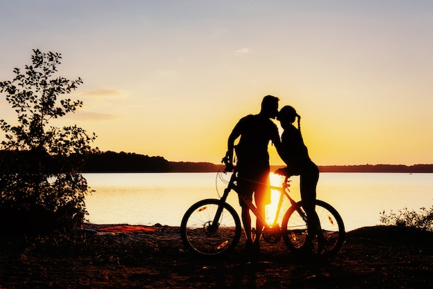 Pareja en bicicleta al atardecer junto al lago