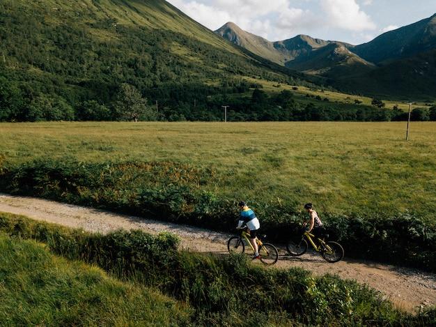 Pareja en bicicleta por una carretera en las tierras altas de escocia
