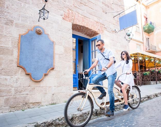 Pareja en bicicleta tándem en la calle de la ciudad contra el fondo de la pared y puertas retro
