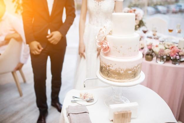 Pareja de boda cortando pastel de bodas