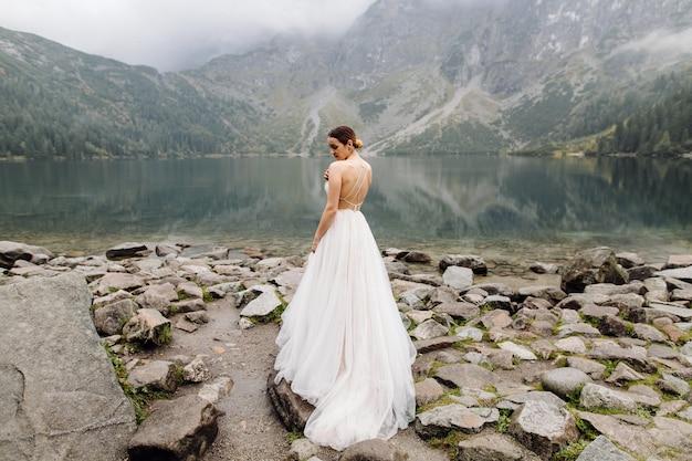 Pareja de boda romántica en pie de amor del lago sea eye en polonia. montes tatra.