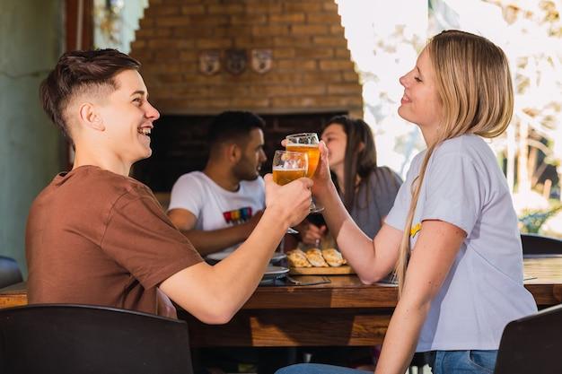 Pareja brindando cerveza en el bar restaurante al aire libre. concepto de estilo de vida con gente feliz divirtiéndose juntos. concéntrese en la pareja de delante.