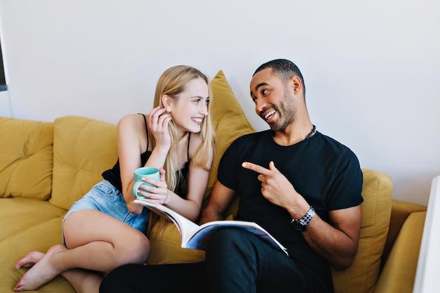 Pareja bromeando, hablando, divirtiéndose, sonriendo sofá en casa. los amantes se relajan, leen una revista, beben té. estado de ánimo positivo, bromas en la conversación