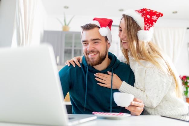 Pareja busca algo en la computadora para unas vacaciones de navidad