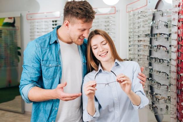 Pareja buscando gafas nuevas en óptico