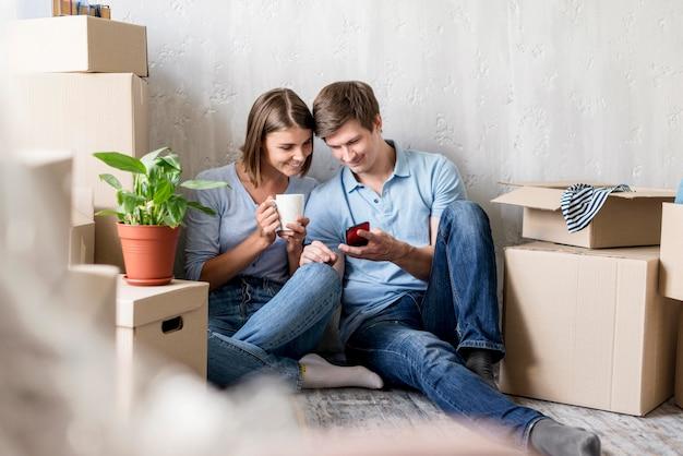 Pareja con café y smartphone mientras empaca para mudarse de casa