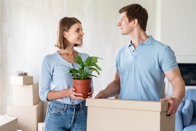 Pareja con caja y planta lista para mudarse