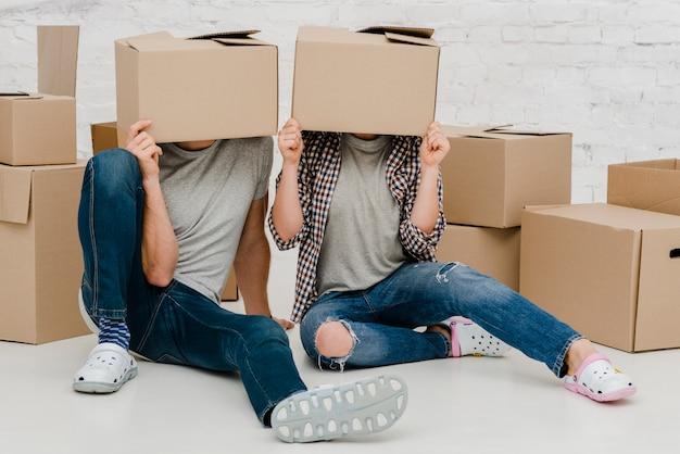 Pareja con cajas de cartón en las cabezas