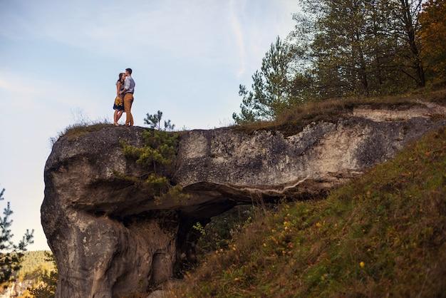 Pareja en cálidos abrazos en ropa casual quedándose en la cima de la roca al amanecer o al atardecer.