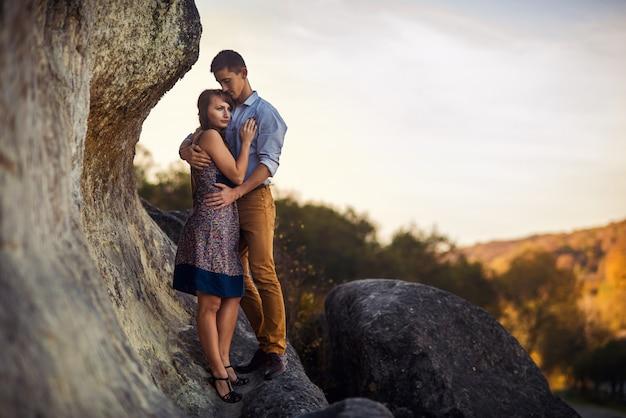 Pareja en cálidos abrazos en ropa casual quedándose en la roca al amanecer o al atardecer.