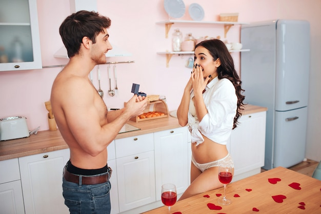 Pareja caliente de pie en la cocina. joven mantenga caja con anillo. él hace proposición a la mujer. ella se ve feliz y emocionada. están medio desnudos.