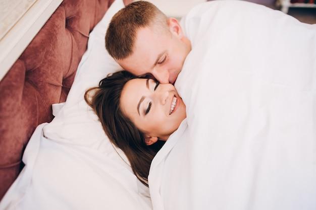 Pareja en la cama feliz niña y novio debajo de las sábanas.