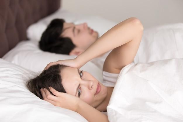 Pareja en la cama, mujer que sufre de insomnio, dolor de cabeza, ronquidos