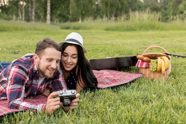 Pareja con una cámara sobre manta de picnic