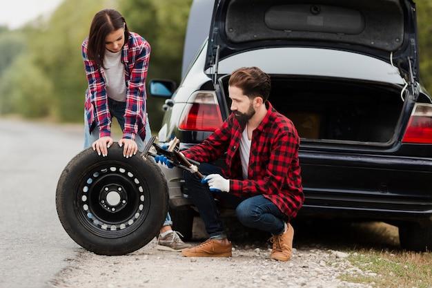 Pareja cambiando el neumático del coche juntos