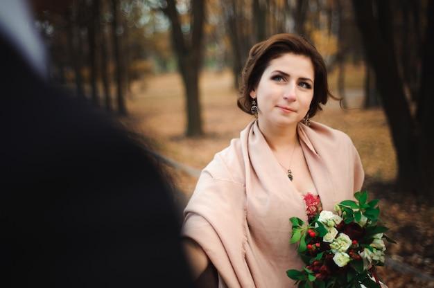 Pareja camina en el parque. abrazo romántico de los recién casados.