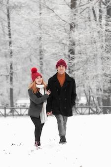 Pareja caminando alegremente en un parque nevado congelado