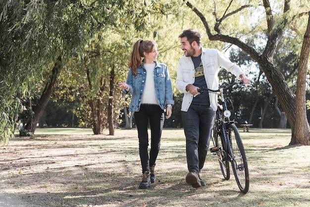 Pareja caminando con bicicleta en el parque