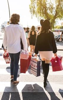 Pareja caminando en la calle con bolsas de compras