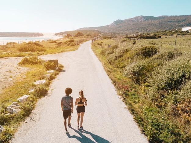 Pareja caminando por la carretera entre el mar y las colinas