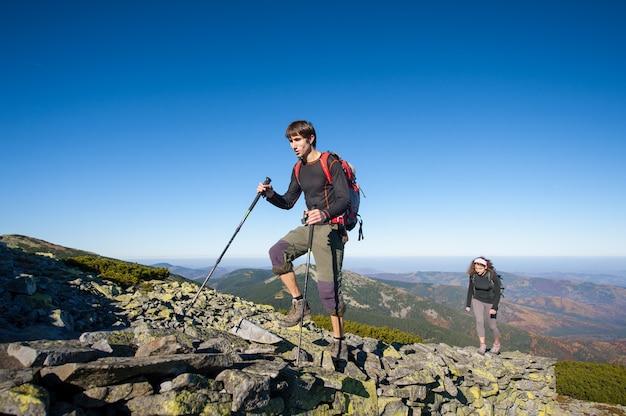 Pareja caminando por la cima de la montaña rocosa, de gran altura.