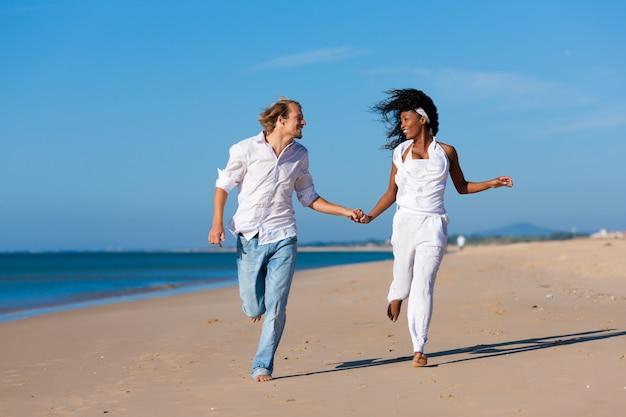 Pareja caminando y corriendo en la playa