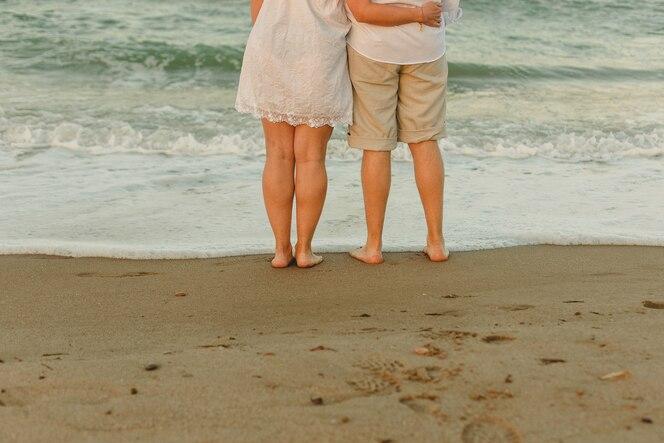 Pareja caminando en la playa tomados de la mano