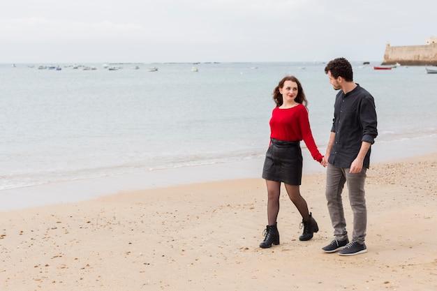 Pareja caminando y hablando en la orilla del mar de arena